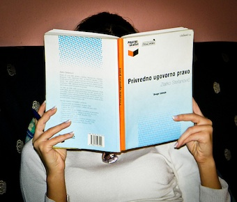 A female student reading a Serbian contract law book, her face is obscured by the book