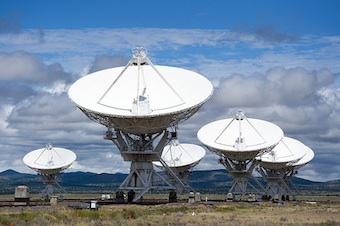 A number of radio telescopes, positioned close together pointed at a cloudy sky